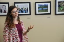 Woman speaking to others at an exhibit with pictures behind her