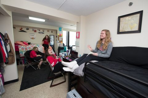 women laughing and sitting on furniture in a residence hall room