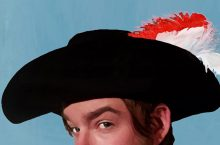 Image from production poster of man wearing a feathered hat