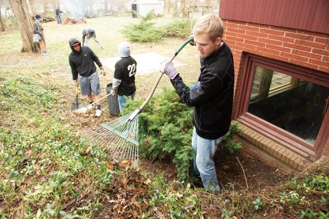 Last April, more than 170 students spread out across Bloomington-Normal to lend a hand to residents and community organizations for the 10th annual Bring It Back to Normal. Students raking and do outside chores at a home.