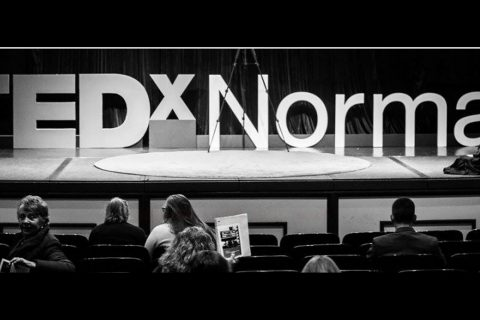 Large letters on a stage spelling out TEDxNormal