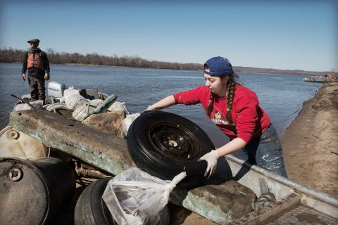 Illinois State student Kaitlyn Remian loads a discarded tire onto a boat on the Mississippi River as part of a cleanup during an Alternative Breaks trip to Grafton, Illinois.