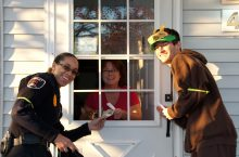 Two students stand at a door to collect a donation from a resident