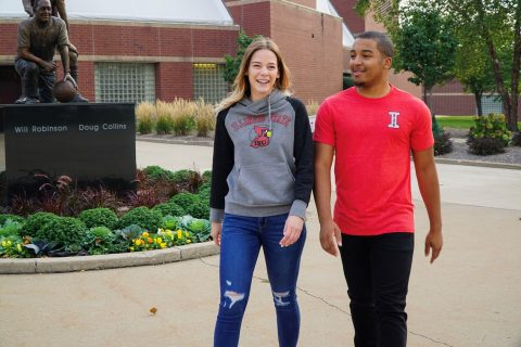 Two students walking on campus and wearing vintage Redbird apparel.