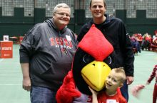 Two adults, a child and Reggie Redbird