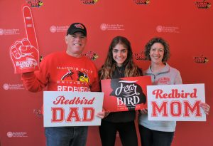 A family poses in front of a photo wall at Family Weekend