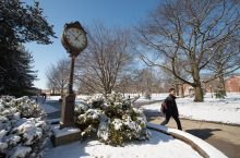 A student walks by a clock on Illinois State's Quad.