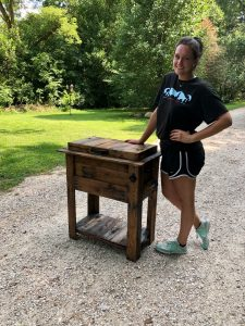 Kendra Cranford with wooden furniture outside