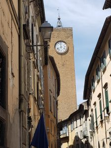 An alley in Orvieto with a clocktower emerging from the surrounding buildings