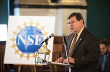 Larry Dietz at a podium with a poster with the letters NSF on it at his side