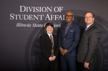 Three Hall of Fame inductees standing in front of a Student Affairs backdrop