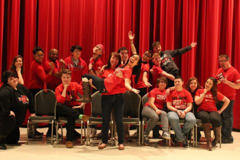 conference staff and students pose together in front of red background