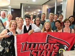 Communication Sciences and Disorders alumni in Italy holding an Illinois State University flag