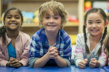 image of children smiling with elbows on a table