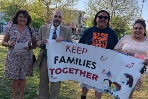 Four people holding a banner with the words Keep Families Together on it.