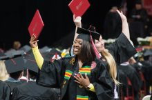 two graduates holding up diplomas