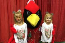 two face-apinted little girls posing with Reggie Redbird