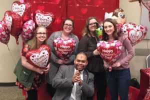 Five students with heart shaped balloons