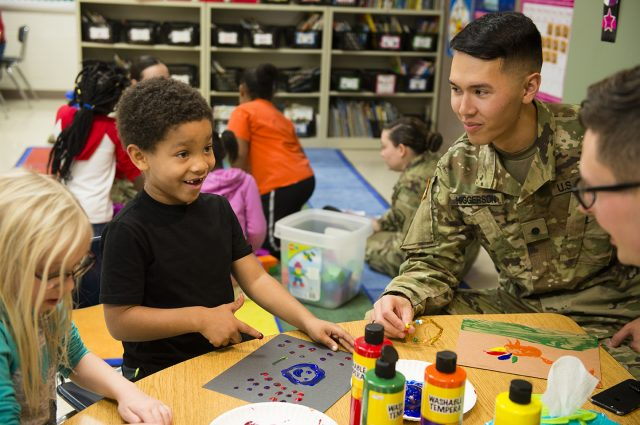 Cadet Matthew Higgerson, a sophomore, works on a finger-painting project with first graders at Fox Creek Elementary.