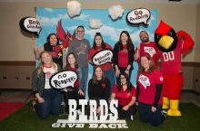 Staff and students from the Dean of Students Office taking their photo for Birds Give Back.