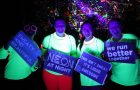 group of people holding signs at night for the neon fun run