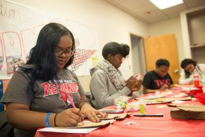 Students decorate bags at a table