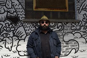 Poet Amish Trivedi stands in front of a mural.