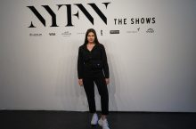 Madison Stoneman standing in front of New York Fashion Week white backdrop