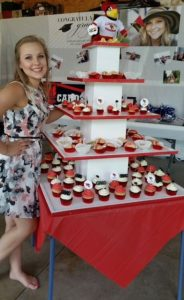 A Future Redbird poses with their red and white graduation cupcake display