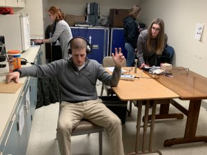 Student receiving a hearing test from another student