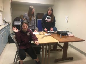 Students giving a student a hearing test