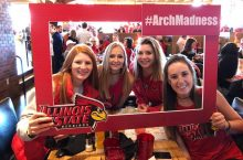 4 female Redbird fans hold an #ArchMadness sign