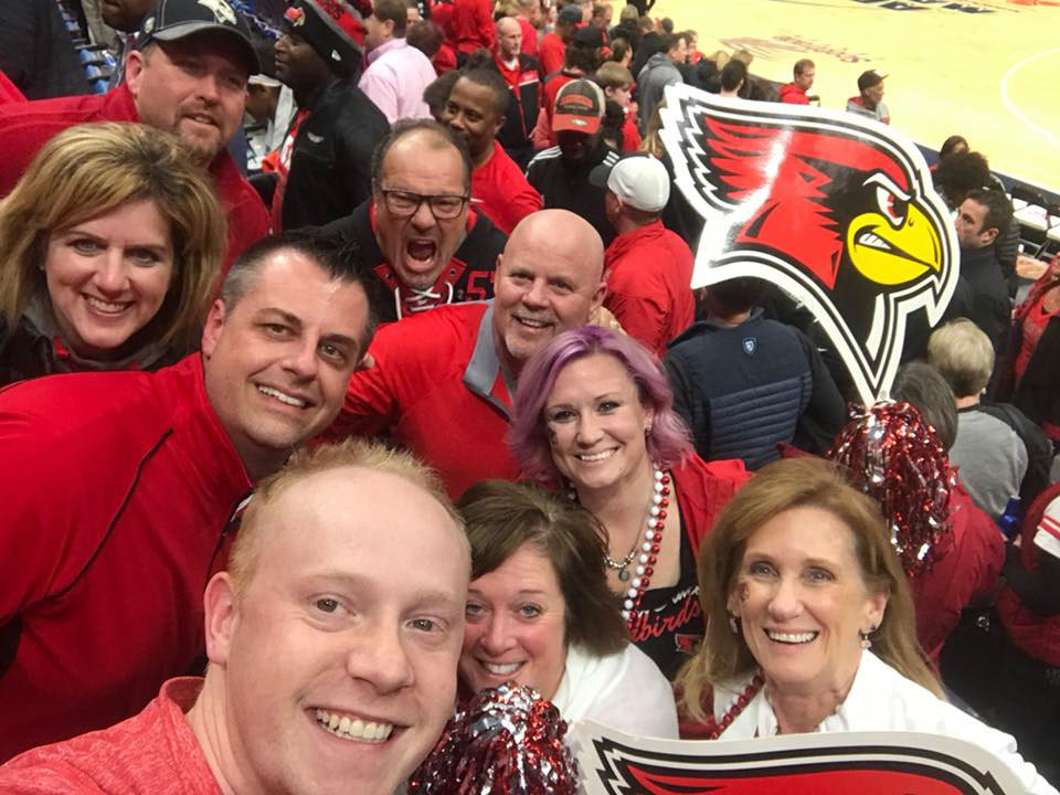 A group of Redbird fans poses in front of the basketball court at Arch Madness