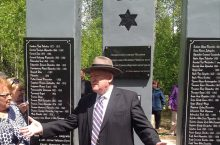 man standing in front of monunment with Star of David and plaques of names