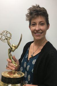 woman holding Emmy statuette.