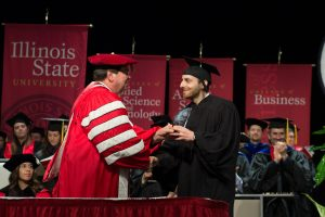 Sam Alex receives the Outstanding Young Alumni Award from Illinois State University President Larry Dietz at the 2019 Founders Day Convocation.