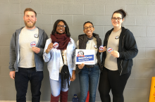 four people with AmeriCorps sign