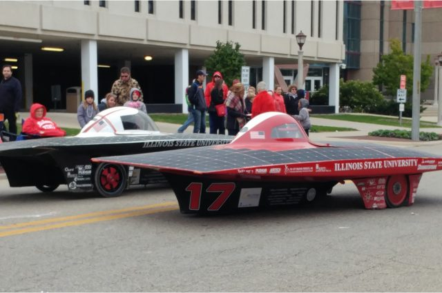 two solar cars side-by-side in front of Julian Hall