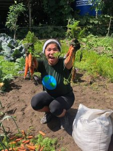 Student holding carrots and smiling