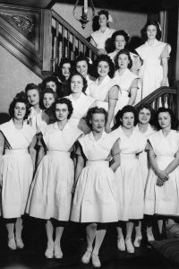 Black and white photo of a housemother with her 17 female nursing students.