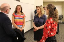 Jessica Lizzio (left), Amanda Lawler, and Brooklyn Jewsberry talk with their client after their ICC presentation. They worked with the environmentally focused nonprofit.