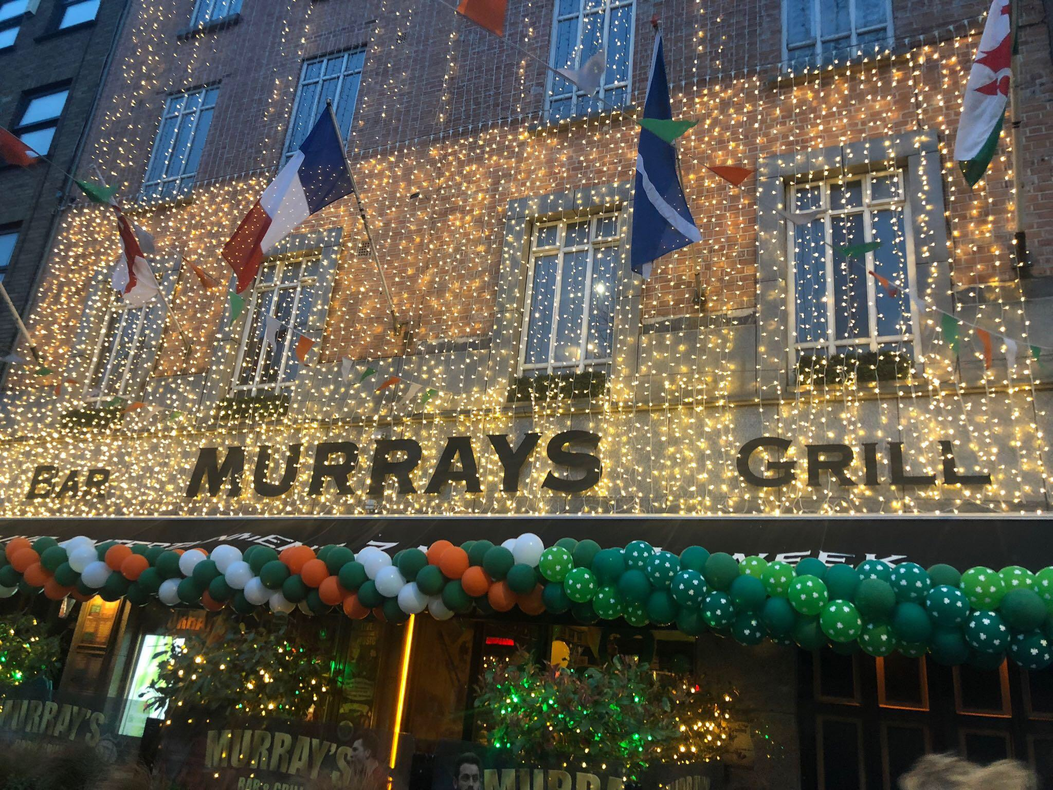 sign of Murray's Bar & Grill decorated for St. Patrick's Day with lights and balloons