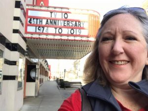 TV-10 News Director Laura Trendle Polus in front of TV-10 anniversary movie marquee
