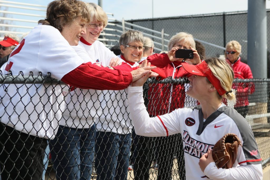 Current Redbird softball player Annie Borries greets 1969 team members Jan Stuckey and Tudy Schmied as their former teammate Karen Roppa looks on.