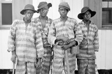 Four men standing in prison uniforms