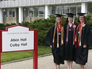 Three students in ISU regalia 2013 outside Atkin/Colby hall (now demolished)