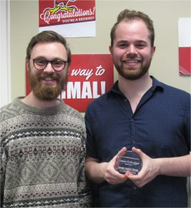 Two men, one holding an award