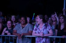 A group of students with glowsticks and big smiles enjoying a concert