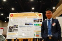 Hu Xi presents at ASC 2019 International Conference. He poses in front of research poster.