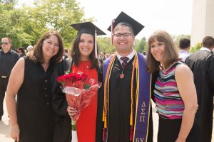 Illinois State students pose with parents at graduation